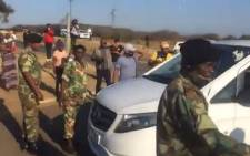 A screengrab of a small group of people dressed in uMkhonto weSizwe Military Veterans Association (MKMVA) uniforms blocking a police vehicle trying to make its way into former President Jacob Zuma's Nkandla homestead on 7 July 2021.
