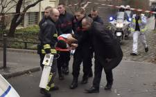 A victim is evacuated on a stretcher on 7 January, 2015 after armed gunmen stormed the offices of the French satirical newspaper Charlie Hebdo in Paris, leaving at least 11 people dead. Picture: AFP.