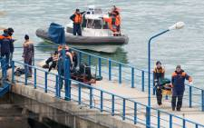 FILE: Russian rescuers carry a stretcher with passenger belongings after a Russian military plane crashed in the Black Sea, on a pier outside Sochi, on December 25, 2016. Picture: AFP