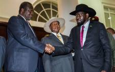 In this file photo taken on 7 July 2018 President of South Sudan, Salva Kiir (R), shakes hands with opposition leader Riek Machar (L) during peace talks at Uganda's statehouse in Entebbe where they were received by Ugandan President Yoweri Museveni (C). Picture: AFP