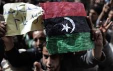 A Libyan demonstrator holds his country's old flag during a protest in the eastern city of Tobruk on February 25, 2011.