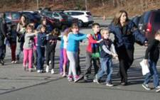 Children from the Sandy Hook Elementary School are led away from the premises after a gunman opened fire, killing more than 20 people on December 14, 2012. Picture: AFP.