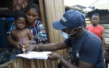Bidemi Aye receives a pre-paid debt card for cash and food provided by the World Food Programme (WFP) in a makeshift home in the Makoko riverine slum settlement in Lagos, Nigeria, on 27 November 2020.  Picture: AFP.