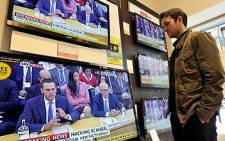 A man watches televisions on 19 July 2011, showing News Corporation Chief Rupert Murdoch giving evidence to a Parliamentary Select Committee on the phone hacking scandal. Picture: AFP