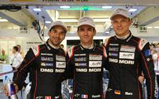 Swiss driver Neel Jani (L), who took the pole position with best time at 3 16. 887 with his Porsche 919 - Hybrid N18, celebrates with teammates Romain Dumas of France (C) and Germanys Marc Lieb (R) after the qualifying practice session of the 83rd Le Mans 24-hours endurance race on 11 June, 2015 in Le Mans, western France. Picture: AFP.