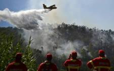 FILE: Firefighters watch a firefighter plane trying to extinguish a wildfire at Monchique, Algarve, southern of Portugal. Picture: AFP.