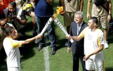 Brazilian former footballer Lucio (R) and Brasilia's governor Rodrigo Rollemberg receive the Olympic flame from fireman Haudson Alves at the field of the Brasilia National Stadium in Brasilia on 3 May 2016. Picture: AFP