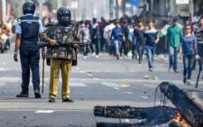 FILE: Security personnel stand guard near a fire on a road during a curfew in Guwahati on 12 December 2019, following protests over the government's Citizenship Amendment Bill. Picture: AFP.