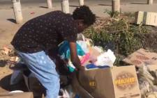 This young man rummages through garbage in Zandspruit to find food and anything else that's useful. He knows about COVID-19 and the lockdown but has to attend to more pressing needs, like getting food into his stomach. Picture: Theto Mahlakoana/EWN