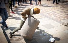 A student tries to break a concrete dustbin for ammunition during skirmishes with private security at Senate House at Wits University. Picture: Nina Leslie/i-Witness