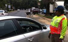 A Johannesburg metro police officer pulls a motorist to the side of the road. Picture: Tshepo Lesole/EWN
