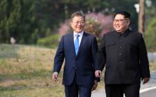 North Korea's leader Kim Jong Un (right) and South Korea's President Moon Jae-in (left) walk together after a tree-planting ceremony at the truce village of Panmunjom on 27 April 2018. Picture: AFP