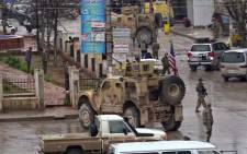 An image grab taken from a video obtained by AFPTV on 16 January 2019 shows US troops gathered at the scene of a suicide attack in the northern Syrian town of Manbij. Picture: AFP.