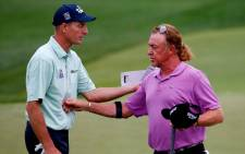 Jim Furyk of the United States and Miguel Angel Jimenez of Spain shake hands on the 18th green during the second round of the 96th PGA Championship at Valhalla Golf Club on August 8, 2014 in Louisville, Kentucky. Picture: AFP.
