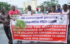 Liberians hold a banner during a demonstration over the disappearance of newly printed bills, on 24 September, 2018, in the capital Monrovia. Picture: AFP
