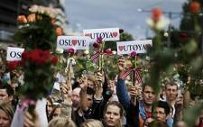 "People hold flowers and love ""Utoeya"" and ""Oslove"" signs as thousands of people massed outside Oslo's City Hall on July 25, 2011. Picture: AFP"