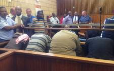 """Four police officers accused of the murder of 32-year-old Khulekani Mpanza hide their faces in the Krugersdorp Magistrates Court on 3 November 2015. Picture: Mia Lindeque/EWN"
