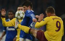 FILE PICTURE: Schalke's Dutch striker Klaas-Jan Huntelaar (L) and Arsenal's German striker Lukas Podolski vie for the ball during a UEFA Champions league football match. Picture: AFP