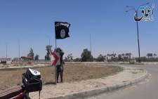 An image grab taken from a video uploaded on May 18, 2015 by Aamaq News Agency, a Youtube channel which posts videos from areas under the Islamic State (IS) group's control, allegedly shows an IS fighter hanging a flag of the group in a street of Ramadi, the Iraqi capital of Anbar province, a day after the city was captured by IS. Picture: AFP/HO/Aamaq.