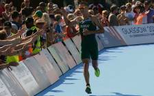 Triathlete Richard Murray acknowledges the crowd as he heads down the home straight in the men's event at the 2014 Commonwealth Games. Picture: SASCOC
