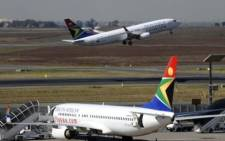 FILE: A South African Airways flight takes off as another one is parked in a bay on the tarmac at OR Tambo International airport in Johannesburg. Picture: AFP