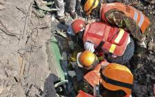 Rescue and medical personnel try to free a woman who discovered alive 5 May 2016 after being trapped for six-days in the rubble of a residential house that collapsed during torrential rain in Kenyan capital. Picture: AFP.