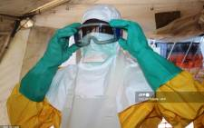 This file photo taken on 28 June 2014 shows a member of Doctors Without Borders (MSF) putting on protective gear at the isolation ward of the Donka Hospital in Conakry, where people infected with the Ebola virus are being treated. The World Health Organization on 19 June 2021 officially announced the end of Guinea's second Ebola outbreak which was declared on 14 February. Picture: AFP