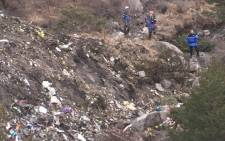 A screengrab taken from an AFP TV video on March 24, 2015 shows search and rescue personnel near scattered debris while making their way through the crash site of the Germanwings Airbus A320 that crashed in the French Alps above the southeastern town of Seyne. Picture: AFP.