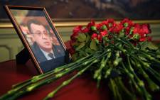 Flowers are placed in front of a portrait of Andrey Karlov in the Foreign Ministry in Moscow on 20 December, 2016, a day after the assassination of the Russian ambassador in the Turkish capital. Picture: AFP.