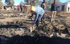 A Primrose informal settlement resident cleans up after a fire gutted their homes on 22 August. Picture: Mia Lindeque/EWN