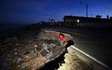 FILE: A reporter walks on the debris of a washed out highway in Flagler Beach, Florida, on October 8, 2016. Picture: AFP