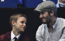 Former england footballer David Beckham (R) and his son Romeo (L) applaud while watcing the round robin stage men's doubles match between Brazil's Bruno Soares and Britain's Jamie Murray and Croatia's Ivan Dodig and Brazil's Marcelo Melo on day five of the ATP World Tour Finals tennis tournament in London on November 17, 2016. Picture: AFP.