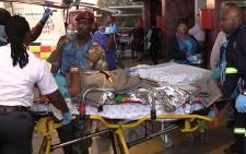 A victim of the Nigerian building collapse is stretchered into the Steve Biko Academic Hospital on Monday 22 September 2014. Picture: Vumani Mkhize/EWN.