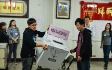 Election officials display an unopened ballot box prior to counting votes at a polling station in Taipei on 11 January 2020. Picture: AFP