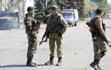 Ukrainian servicemen stand guard on 7 September, 2014 at a Ukrainian army checkpoint on the outskirts of the key southeastern port city of Mariupol, after an overnight bombing attack. Picture: AFP.