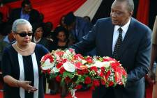 KENYA, Nairobi : Kenyan President Uhuru Kenyatta and his wife Margaret lay a wreath of flowers during the funeral service of his nephew Mbugua Mwangi and his fiancee Rosemary Wahito in Nairobi on September 27, 2013 after they were both killed in the Westagte Mall attacks. Kenyan and foreign forensics teams scoured the wreckage of a Nairobi shopping mall for bodies and clues after a four-day siege by Islamist gunmen left 67 dead and dozens more missing. AFP PHOTO/JOHN MUCHACHA