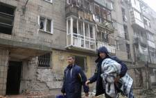 FILE: Local people walk past damaged buildings after overnight shelling in Donetsk, Ukraine. A new wave of violence was reported although a cease-fire was declared in the main separatists city. Picture: EPA.