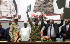 "FILE: Sudan's protest leader Ahmad Rabie (2nd-R), flashes the victory gesture alongside General Abdel Fattah al-Burhan (C), the chief of Sudan's ruling Transitional Military Council (TMC), during a ceremony where they signed a 'constitutional declaration' that paves the way for a transition to civilian rule, in the capital Khartoum on 17 August 2019, accompanied by General Mohamed Hamdan Daglo ""Hemeti"" (2nd-L), TMC deputy chief and commander of the Rapid Support Forces (RSF) paramilitaries, Ethiopian Prime Minister Abiy Ahmed (L), South Sudan President Salva Kiir Mayardit (2nd-R, behind), Chadian President Idriss Deby (3rd-L), and Kenyan President Uhuru Kenyatta (R). Picture: AFP."