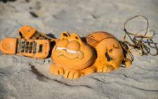 Spare parts of plastic 'Garfield' phones are displayed on the beach on 28 March 2019 in Plouarzel, western France, after being collected from a sea cave by environmental activists. Picture: AFP.