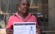 Abraham Nqulungu holds a picture of his sister, Mercy, who has been missing since August. Picture: Masego Rahlaga/EWN.