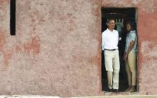 US President Barack Obama and his wife Michelle look out from the Door of No Return while touring the House of Slaves, or Maison des Esclaves, at Goree Island off the coast of Dakar, Senegal on 27 June 2013. Picture: AFP