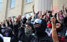 Demonstrators raise their fists as they gather on the steps of the Louisville Metro Hall on 24 September 2020 in Louisville, Kentucky. Picture: AFP