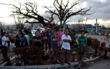 People stand on a corner at the airport watching aid flights land in Tacloban. Picture: AFP.