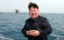 FILE: This undated picture released from North Korea's official Korean Central News Agency (KCNA) on 9 May 2015 shows North Korean leader Kim Jong-Un smiling while observing an underwater test-fire of a submarine-launched ballistic missile at an undisclosed location at sea. Picture: AFP.