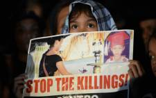 A young protester holds a placard during a demonstration against the killings of suspected drug users allegedly by police during anti-drugs raids in Manila on 21 August 2017. Picture: AFP.