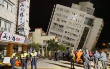 FILE: Rescue workers block off the area to search for survivors outside a building which tilted to one side after its foundation collapsed in Hualien after a strong 6.4-magnitude quake rocked eastern Taiwan early on 7 February 2018. Picture: AFP.