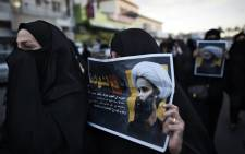 Bahraini women hold posters bearing portraits of prominent Shiite Muslim cleric Nimr al-Nimr during a protest against his execution by Saudi authorities, in the village of Jidhafs, west of the capital Manama on 3 January, 2016. Picture: AFP.