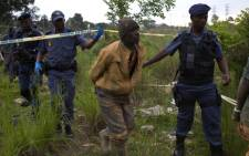 FILE: South African police escort illegal miners arrested for illegal mining and trespassing on 7 January, 2014 in Johannesburg. Picture: AFP.