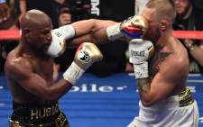 Floyd Mayweather Jr. and Conor McGregor trade punches during their super welterweight boxing match on 26 August, 2017 at T-Mobile Arena in Las Vegas, Nevada. Picture: AFP.