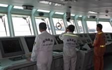 The Nanhai Rescue Bureau rescuers searching for survivors in the water after the Marshall Islands-registered MOL Motivator (in background R) collided with a Chinese cargo ship, the Zhong Xing 2, off Hong Kong waters on 5 May 2014. Picture: AFP.